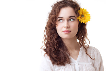 Young beautiful girl with yellow flower in her hair isolated on