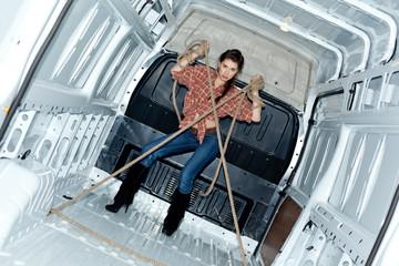 Sexy young woman in cargo van inside