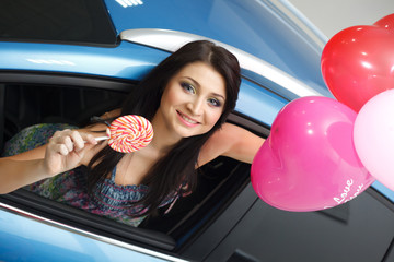 Young woman with candy and heart baloons with New car