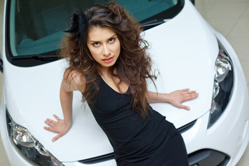 Young woman on white hood of New car