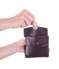 Female hand putting Polish Zloty coin into purse