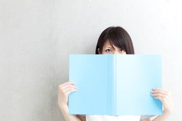 ファイルで顔を隠す女子学生
