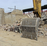 demolition site with excavator,some stone and iron rubble poster