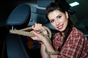 Young woman with rope inside New car with leather interior