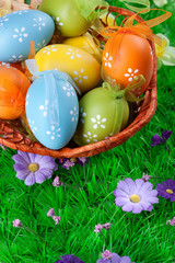 color easter eggs in basket on the green grass