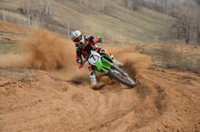 Motocross-Fahrer mit einer starken Steigung biegt scharf