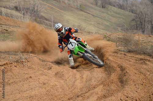 Fototapeta Motocross rider with a strong slope turns sharply