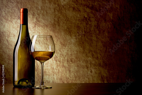 bottle with white wine and glass on a old stone. glass in the fo