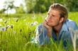 junger mann liegt im gras und relaxt