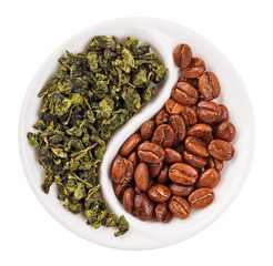 Green leaf tea versus coffee beans in Yin Yang shaped plate, iso