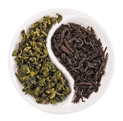 Green leaf tea versus black one in Yin Yang shaped plate, isolat