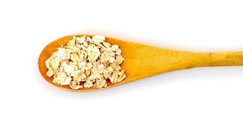 Uncoocked rolled oats in wooden spoon isolated on white
