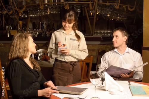 Kelner przyjmujący zamówienie od klientów restauracji