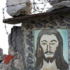 Portrait de Jésus surmonté de fil de fer barbelé.