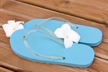 accueil avec sandales bleues et fleurs de frangipanier