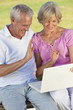 Happy Senior Couple Using Laptop Computer Outside in Sunshine