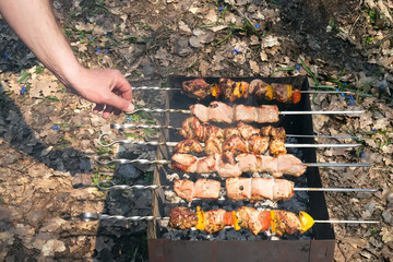 Man's hand turns the skewer with a barbecue on the grill