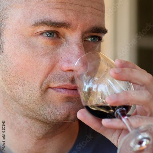 Homme dégustant un verre de vin rouge