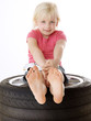 Cute blond girl sitting on summer tyre with a toy car