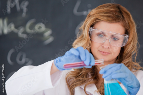 Young female scientist carrying out an experiment