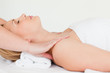 Beautiful blond-haired woman lying down while receiving a spa tr
