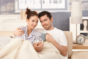 Young couple drinking tea in bed smiling happily