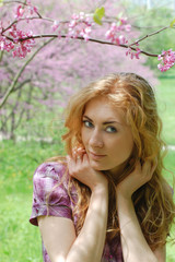 Red-haired woman under viloet flower tree