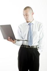 ノートパソコンを見つめながら考え込むビジネスマン