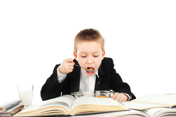 hungry schoolboy eating in the classroom