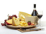Fototapety Cheese still life on a wooden round tray