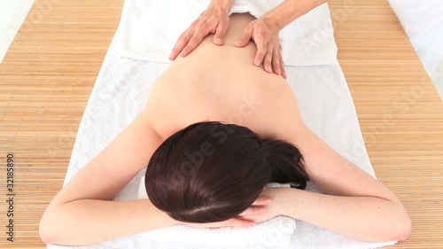 Dark-haired woman been given a massage