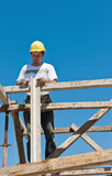 Construction worker on scaffold busy on formwork preparation poster