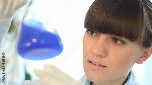 Female scientist examines Erlenmeyer flask, zoom in