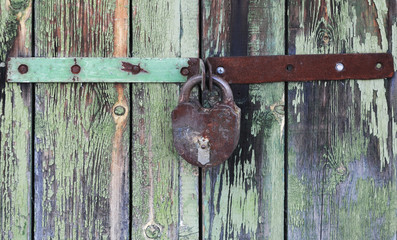 Old wooden doors locked with rusty padlock