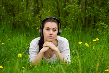 Girl with headphones lying in the grass ans looking streight