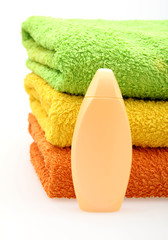 colorful stacked towels and bottle of soap