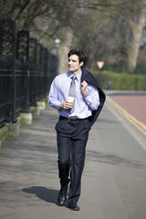 A businessman walking, holding a hot drink