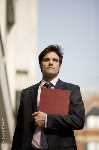 A businessman walking along the street, holding a folder