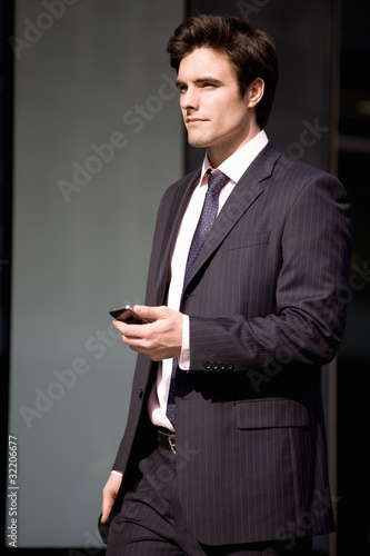 A businessman walkin along the street, holding  his mobile phone