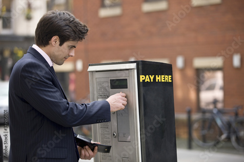 A businessman putting coins in a parking meter