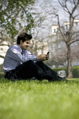 A businessman sitting on the grass, using his mobile phone