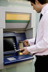 A businessman using a cash machine