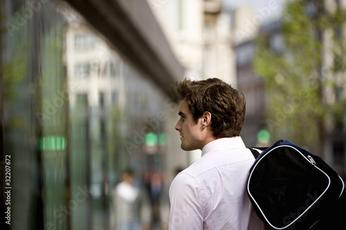 A businessman walking along the street, carrying a gym bag