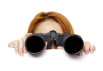 Teen redhead girl with binoculars isolated on white background