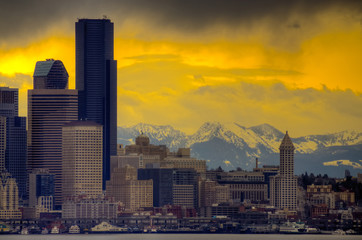 Downtown Seattle with dramatic sky and Cascade Mountains in the