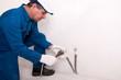 Plumber fixing water pipe