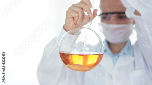 scientist pouring red substance from pipette in Volumetric flask