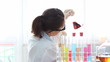 Scientist female mixing Erlenmeyer flask with red substance