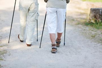 ehepaar unterwegs mit nordic walking stöcken