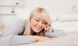 Attractive blond woman talking on cell phone lying down on a car